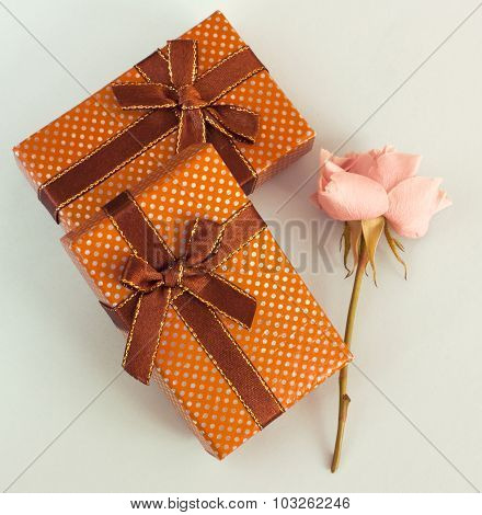 A photo of two gift boxes and a rose
