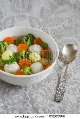 Soup With Chicken Meat Balls, Potatoes, Broccoli And Carrots In A White Bowl, A Healthy And Tasty Lu