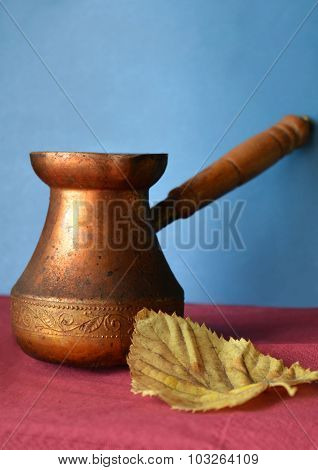 Old copper Turkish coffee pots and yellow autumn leaf on burgundy surface and blue background