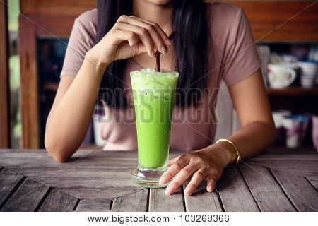 Woman Holding Matcha Green Tea On Wooden Table