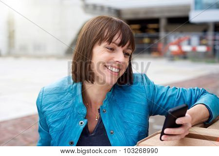 Mature Woman Smiling And Looking At Mobile Phone