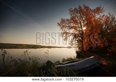 Autumn tree on the coast of the lake highlighted by moon and boat moored on the land