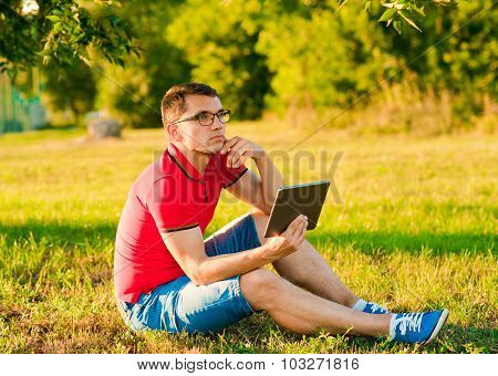 Modern Man Using Tablet Pc Outside On A Autumn Park