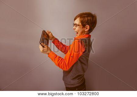 European-looking boy  of ten  years in glasses holding tablet in