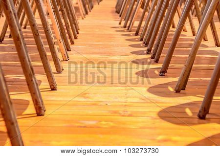 Abstract Old Rusty Metal Chair Legs On A Wooden Floor
