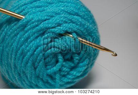 Crochet hook in teal skein of yarn