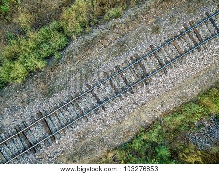aerial view of single railroad tracks in back country with some weeds and trash