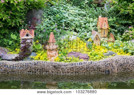 Composition Of Flowers, Shrubs And Garden Figures Near Pond