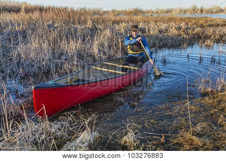 senior male paddling a red canoe through a swamp, early spring