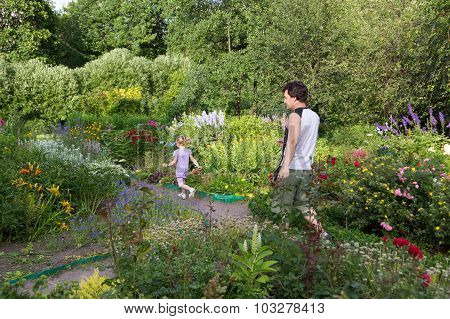 Little Girl And Dad Walking Among Flowers Along Paths Of The Park