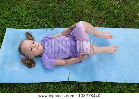 Little Girl With Pigtails Lying On A Mat On Grass