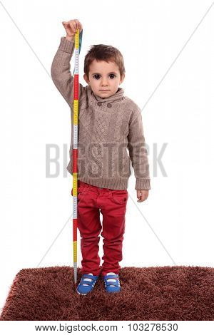 Boy growing tall and measuring himself