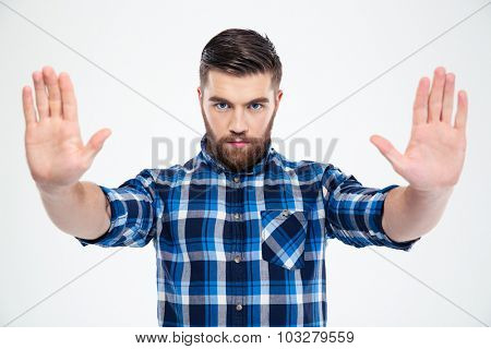 Portrait of a serious man showing stop gesture with palms isolated on a white background