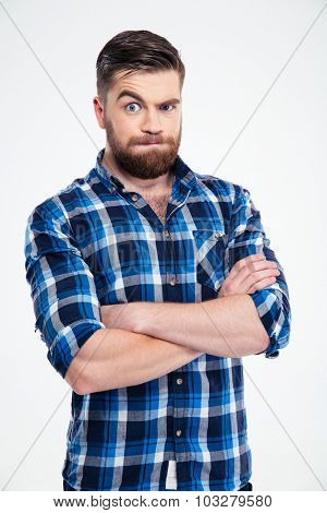 Portrait of amazed casual man standing with arms folded isolated on a white background