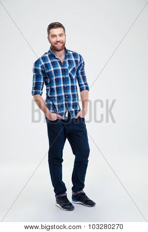 Full length portrait of a smiling casual man standing isolated on a white background