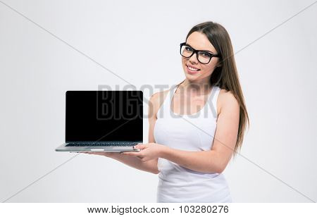 Portrait of a smiling young woman showing blank laptop screen isolated on a white background