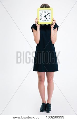 Full length portrait of a young girl covering her face with big clock isolated on a white background