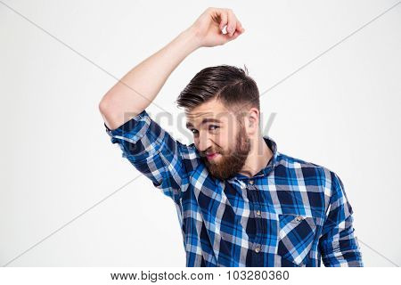 Portrait of a casual man smelling his armpit isolated on a white background