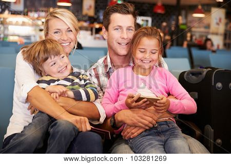 Family In Airport Departure Lounge Waiting To Go On Vacation