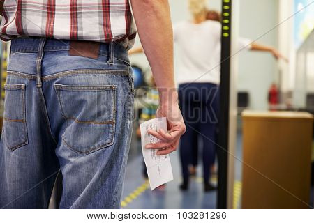 Passenger Passing Through Security Check At Airport