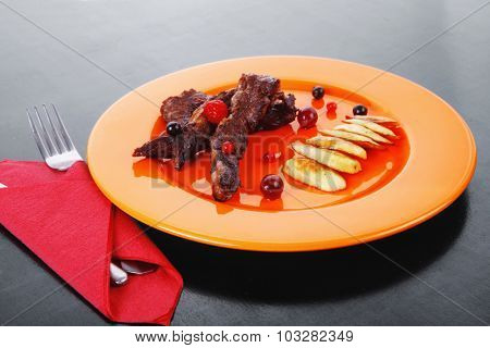 grilled beef meat with berries fried potatoes and cherry under sweet honey sauce on orange plate over black wooden table