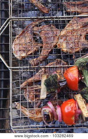 fresh raw lamb ribs on meat holder over fire burned charcoal with vegetable shish kebab on side outdoor party