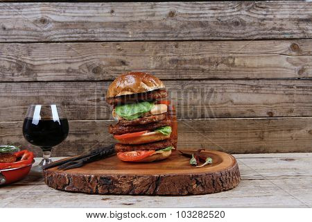 fresh grilled beef huge hamburger served on wood plate with red wine glass chili pepper rosemary green salad leaf and forged vintage antique cutlery over wooden table empty space for text