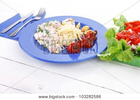 fresh rose wild salmon baked in cream cheese sauce with italian pasta and red hot pepper on blue plate over white wooden table with vegetable salad