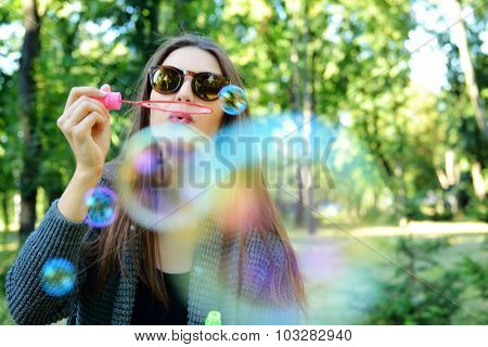 Young woman blowing soap bubbles outdoor in fall park. Image toned and noise added. Soft focus.