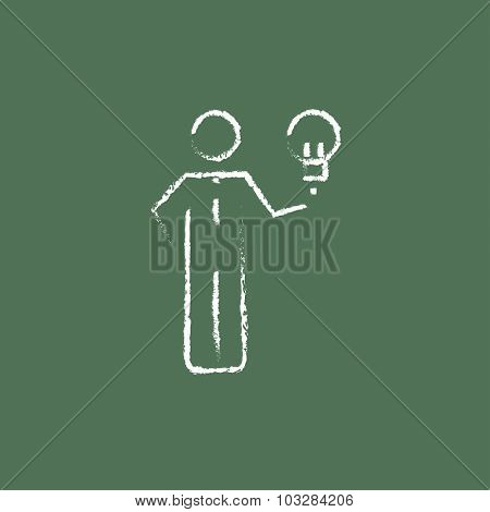 Businessman holding light bulb hand drawn in chalk on a blackboard vector white icon isolated on a green background.