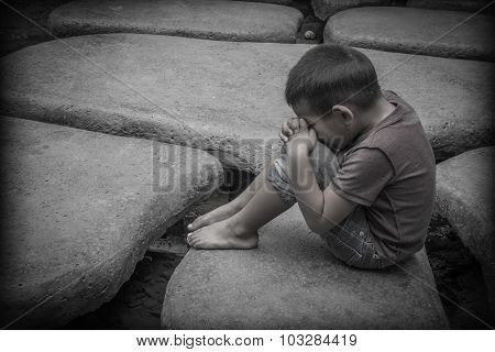 Young Asian child sitting praying on rocks