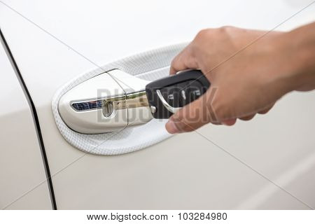 Closeup Of A Woman's Hand Inserting A Key Into The Door Lock Of A White Car