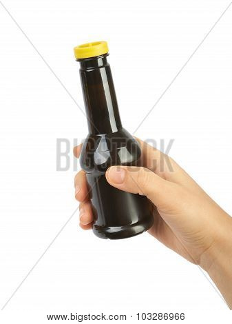 Bottle of soy sauce in the hands isolated on white background