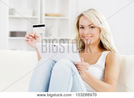 Attractive blond woman with a credit card and a tablet computer.