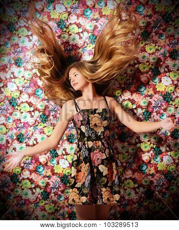 Beautiful girl with magnificent long hair in motion. Floral background. Healthy hair, haircare.