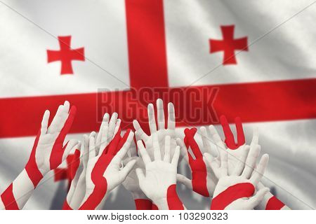 People raising hands in the air against georgian flag with red cross symbols