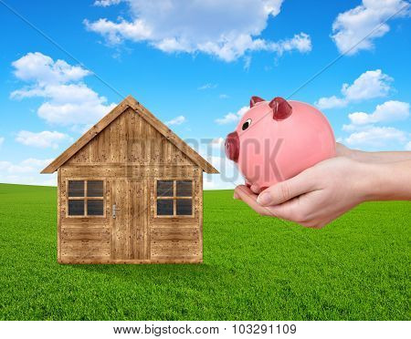 Wooden house on meadow and hand holding a pink piggy bank.