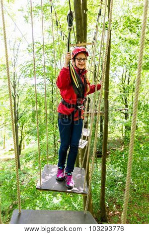 Teenager girl climbing in high rope course or parl