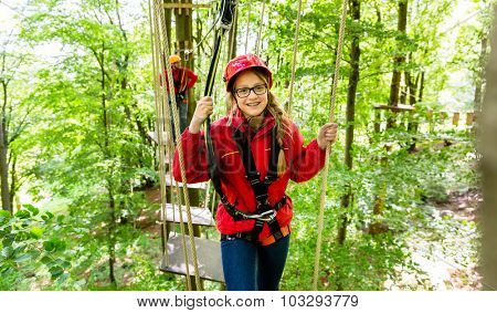 Teenager girl climbing in high rope course or parlor