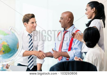 Business handshake in meeting, team of Chinese, Indian and Caucasian ethnicities