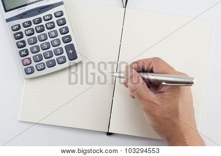 Man hand with pen writing on notepad.
