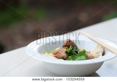 Egg noodle with delicious stewed pork and dumpling in white bowl.