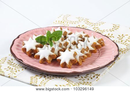 star shaped christmas cookies served on the pink plate with fabric linen