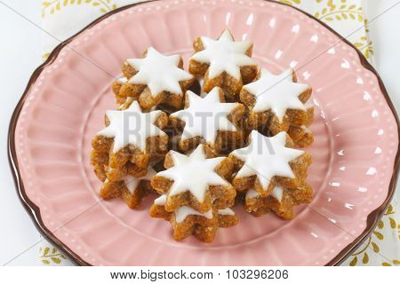 overhead view of pink plate with christmas cookie gingerbread stars with white sugar glaze