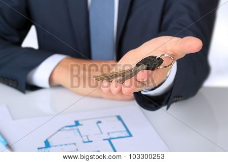 Real-estate Agent Giving  A House  Key. The Plan Of A Flat Behind