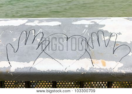 Picture Of Female And Male Hands And Heart On The Parapet Of The Seaside Promenade