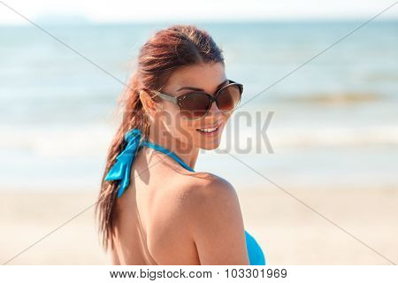 summer vacation, tourism, travel, holidays and people concept -face of smiling young woman in swimsuit with sunglasses on beach