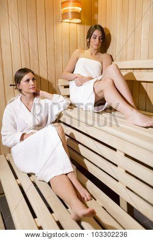 Two Beautiful Women Relaxing In A Sauna