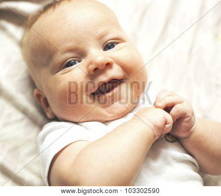 The little baby laughing lying on bed