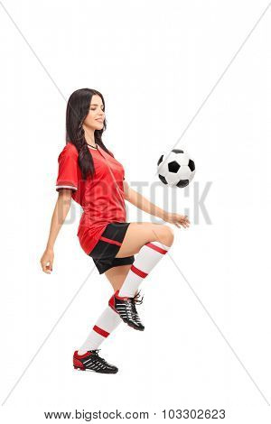 Full length profile shot of a female soccer player juggling a ball on her knee isolated on white background